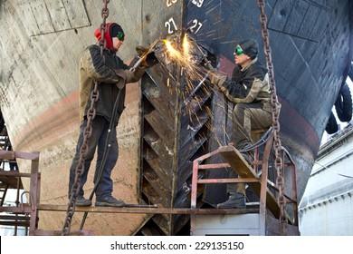 Welders on black metal, repairing a ship in dry dock