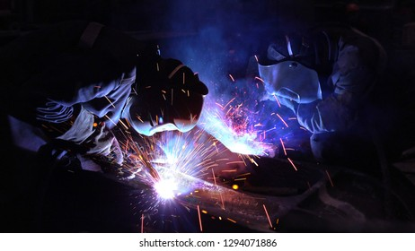 Welders welding metalwork in a factory