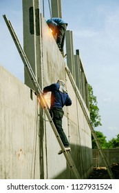 Welders are welding the wall structure at construction site.