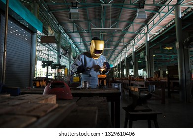 Welders are working to weld metal that has light from welding, splashing out into the workplace, which is an industrial factory with protective sets and masks.