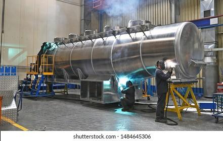 Welding a car tank on an assembly line