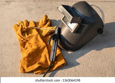 Welding equipment including leather welding gloves, welding mask, handheld welding electrode on concrete floor with orange sunlight.