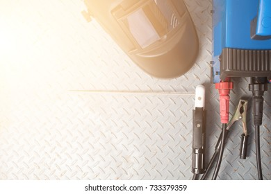 Welding equipment on a metal desk with workshop welding mask,welding electrodes, for arc welding. with copy space for work place in sun rise