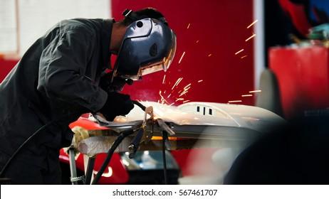 Welding industrial: worker in helmet repair detail in car auto service, telephoto