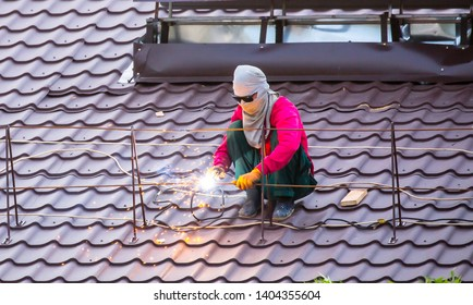 Welding. The master provolit Welding work on the roof with a metal tile. Repair and construction of houses, architecture. Heavy male work, phot with copy space.