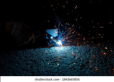 welding of a metal construction on a concrete floor, close-up with a blurred background. MAG welding of metal