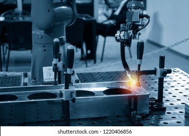 The welding robot machine for welding automotive part in the light blue scene.Industrial 4.0 concept for modern manufacturing process.