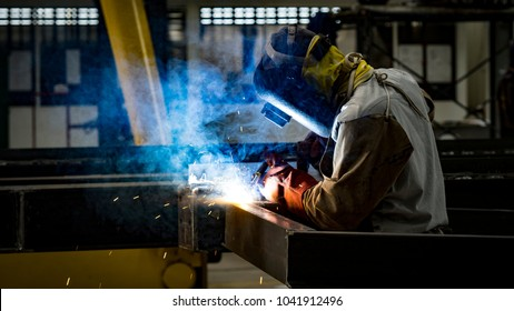 Welding with sparks by Process fluxed cored arc welding ,Industrial steel welder part in factory.