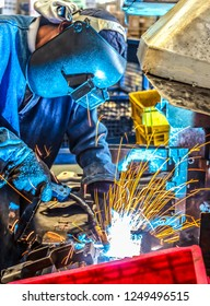 Welding with sparks worker with protective mask metal welding