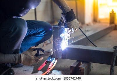 Welding steel by worker in workshop.