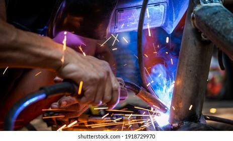 Welding of steel, sparking, not wearing gloves, light colored like fireworks.