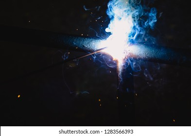 welding steel with sparks lighting in the dark background.