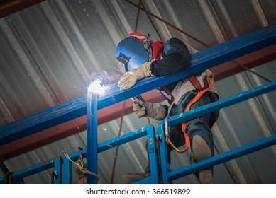 Welding steel worker action in the factory building.