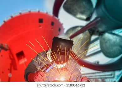 Welding worker in shipyard a large cargo ship repair with spark light, with protective equipment PPE for safe weld in dry dock. on forward Oil Tank ship, propeller ship background shipyard Thailand