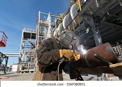 Welding works at installation of the new pipeline on oil refining installation with use of manual arc welding. Fisheye view
