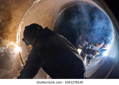 Welding works manual arc welding in the repair of the chemical apparatus by two welders at the same time