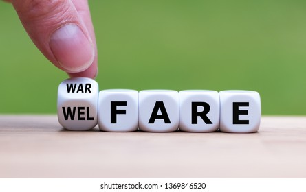 "Welfare instead of warfare. Hand turns a dice and changes the word ""warfare"" to ""welfare""."