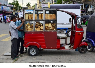 Weligama, Sri Lanka - April, 2017: Man selling bread from his red three wheeled vehicle (tuk tuk) on the street market