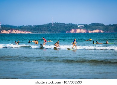 WELIGAMA SRI LANKA - JAN 5, 2017: Unidentified man surfing on a small wave on Weligama beach on Jan 5, 2017. Sri Lanka. It coast of Indian ocean is the best surf paradise in Sri Lanka.