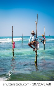 WELIGAMA SRI LANKA - JAN 6, 2017: Unidentified local fishermen are fishing in unique style, sitting on sticks in Weligama on Jan 6, 2017. Sri Lanka. This type of fishing is traditional for Sri Lanka.