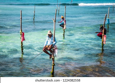 WELIGAMA SRI LANKA - JAN 6, 2017: Unidentified local fishermen are fishing in unique style, sitting on sticks in Weligama on Jan 6, 2017. Sri Lanka. This type of fishing is traditional for Sri Lanka