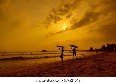 WELIGAMA, SRI LANKA - JANUARY 12 2017: Unidentified couple surfing on sunset on Weligama beach on the coast of Indian ocean  - is the best surf paradise in Sri Lanka