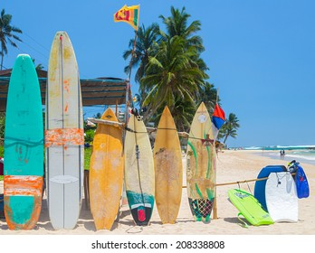 WELIGAMA, SRI LANKA - MARCH 5, 2014: Surf boards on sandy Weligama beach in Sri Lanka. On Weligama beach  surf is available all year around for beginner and advanced.