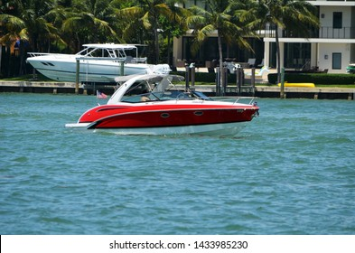 Well appointed cabin cruiser passing Rivo Alto island and upscale island community on Miami Beach,Florida