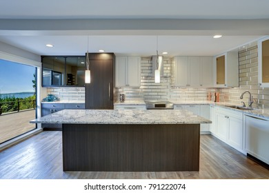 Well appointed kitchen features a large island, gray quartzite countertops,  silver backsplash and white shaker cabinets .