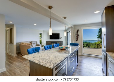 Well appointed kitchen features a large island topped with a gray quartzite countertop and flanked by blue tufted dining chairs with silver nailhead trim.