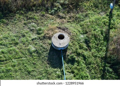 Well of an artesian well with a submersible pump. Covered with a concrete well