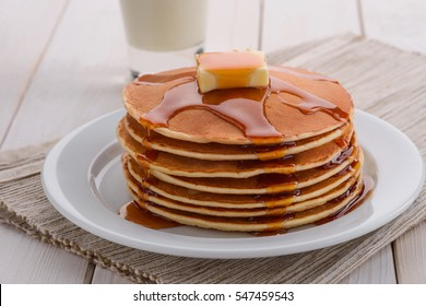 Well baked pancakes are topped with maple syrup for an extra taste. A bite of butter is melting on top of the stack. These pancakes are the one of American meals.