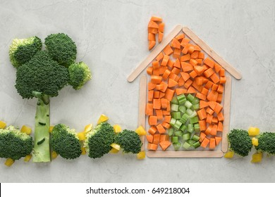 A well being food concept of a house and made of popsicle sticks, carrots, celery, broccoli, and peppers for a healthy, long life. Off white background, horizontal format with copy space.
