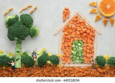 A well being food concept of a house and sun made of popsicle sticks, carrots, celery, broccoli, oranges and miniature people for a healthy, long life. Off white background, horizontal with copy space
