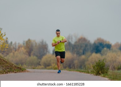 Well built man over 40 wearing activewear training gear looking at his watch