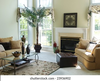 A well decorated family room in a modern american home with an overstuffed sofa, chair and glass coffee table. Large windows make the room very bright and airy.