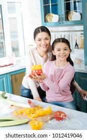 Well done. Beautiful cheerful dark-haired mother and daughter smiling and making a salad and a girl holding some peppers