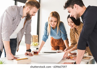 Well done. Creators are looking at sheet of paper with smile. They checking their work in office