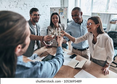 Well done everybody! Top view of young business people toasting each other and smiling while standing in the board room