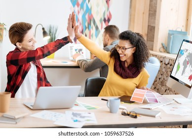 Well done. Good-looking inspired young smart women smiling and giving a high-five while working in the office