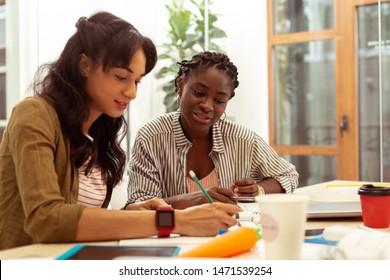 Well done. Pleased dark-skinned tutor sitting near her student while explaining grammar material