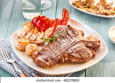 Well done style T bone steak and lobster plate on table beside roasted vegetables side dish and glass of water