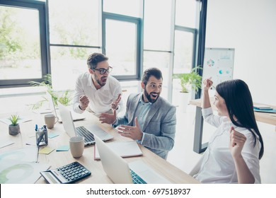 Well done! Success and team work concept. Three business partners are amazed about great news, sitting at the work places next to each other in a row, dressed by the office dress code