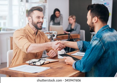 Well done! Two confident young men shaking hands and smiling while sitting at the desk in office with two people working in the background
