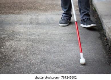 Homem cego bem vestido andando perto de um meio-fio com uma longa bengala branca; fechar-se em cana e pés (espaço de cópia)