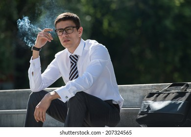 Well dressed business man smoking sitting on a street sidewalk