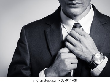 Well dressed businessman fixing his tie.