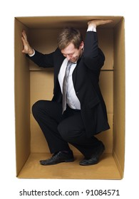 Well dressed businessman in a tight cardboard box isolated on white background