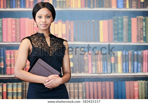 Well dressed and cared for African American woman looking at camera while holding her notebook and digital tablet in her hand in front of her with a shelf of books behind her in the background.