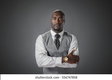 A well dressed confident African American male studio shot with arms crossed and looking at the camera.